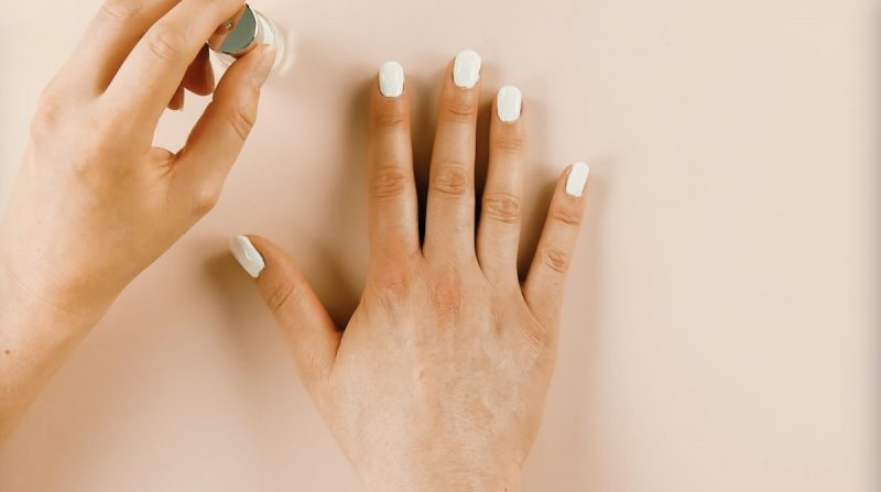 mano destra con smalto per unghie bianco