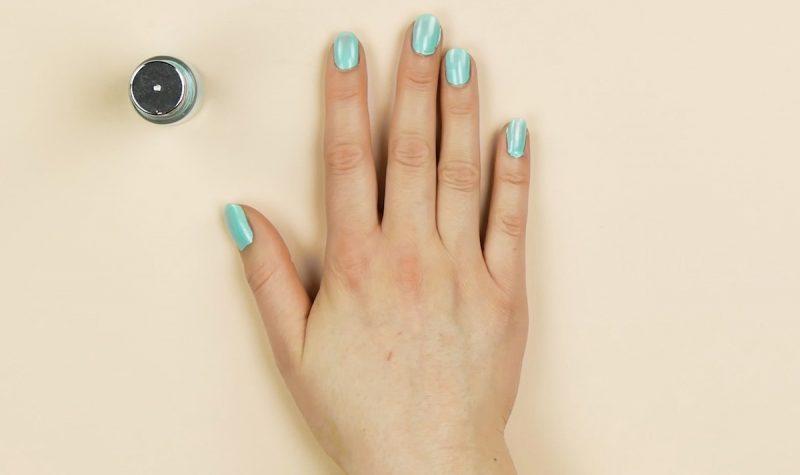 mano destra con smalto per unghie azzurro