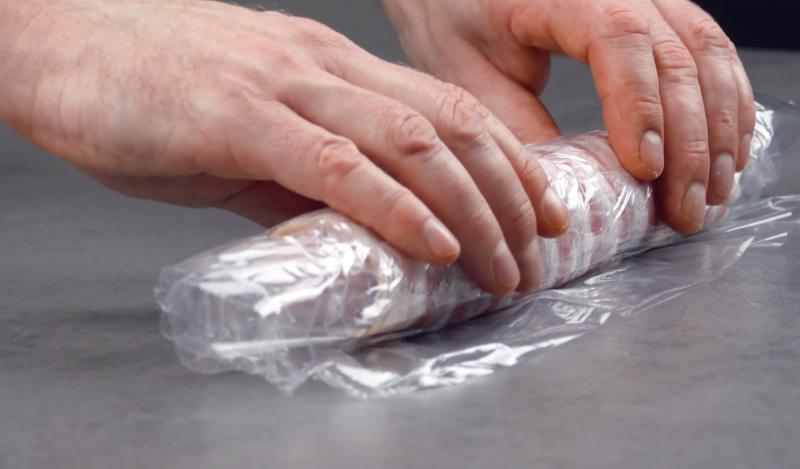 salsicce avvolte da pancetta tesa e pellicola trasparente