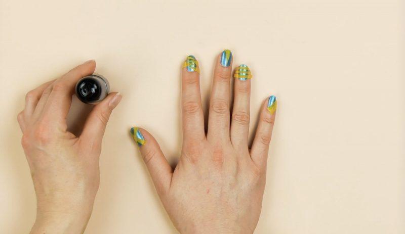 strisce di nastro adesivo sopra le unghie