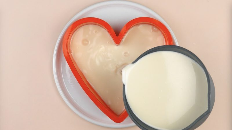 Budino al latte nello stampo per torta a forma di cuore
