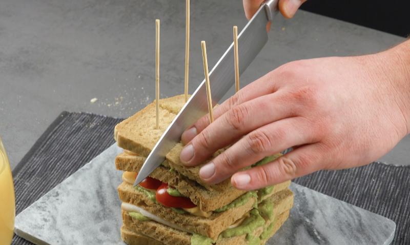 Taglio del toast con crema di avocado, fesa di tacchino e peperone rosso