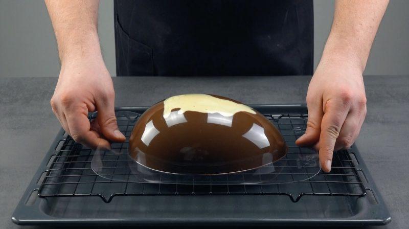 Stampo per uovo di Pasqua con cioccolato fuso a sgocciolare sopra una griglia