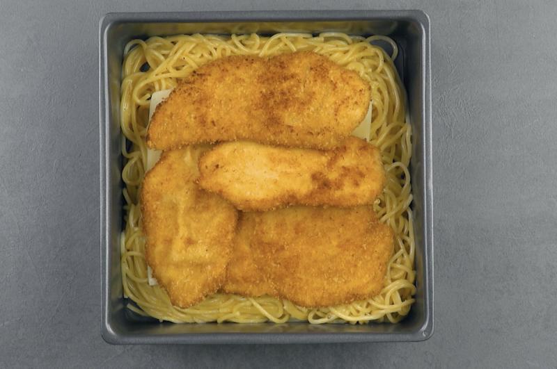 Strato di cotolette di pollo sopra agli spaghetti con il formaggio