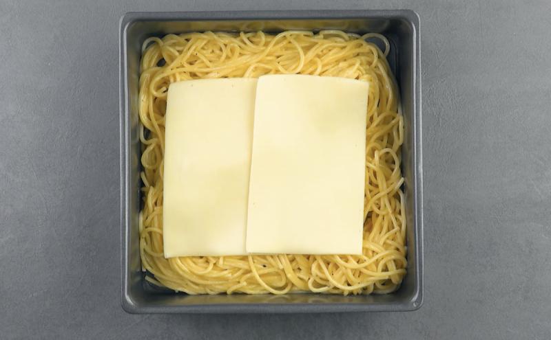 Formaggio a fette sopra agli spaghetti nella teglia