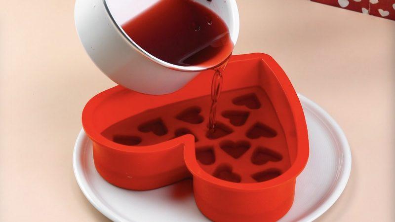 Budino rosso liquido versato nello stampo della torta a forma di cuore