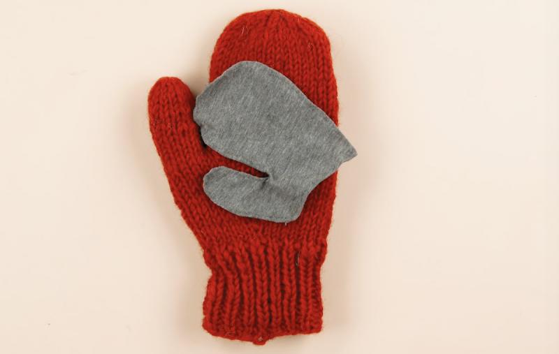 Tessuto a forma ci mano di bambino sopra al guanto di lana