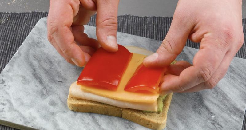 Farcire il toast con crema di avocado, fesa di tacchino e peperone rosso