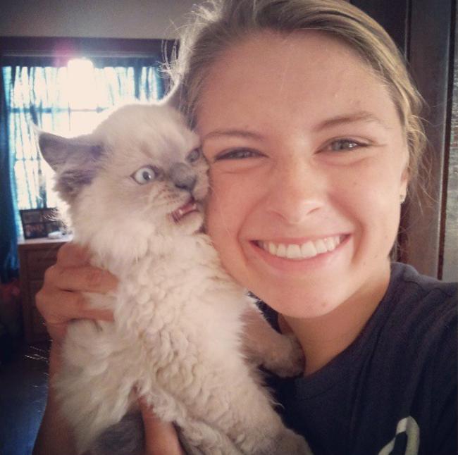 Ragazza avvicina gatto al volto