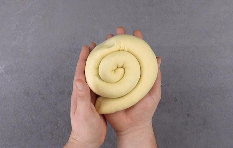 Spirale di pasta lievitata con ripieno alla cannella in mano
