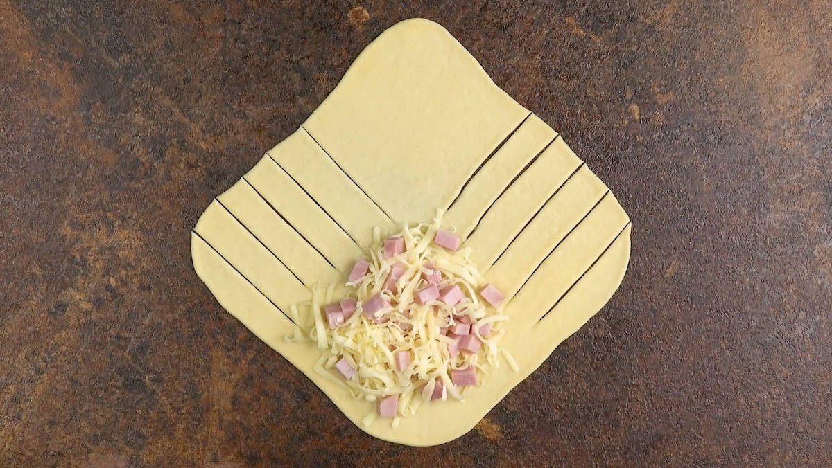 Quadrato di pasta lievitata intagliato con ripieno di prosciutto e formaggio