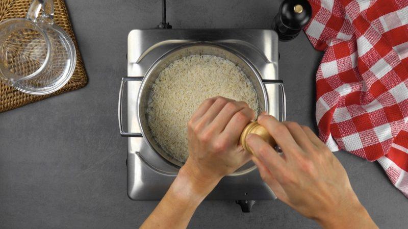Pentola con chicchi di riso condita con sale e pepe