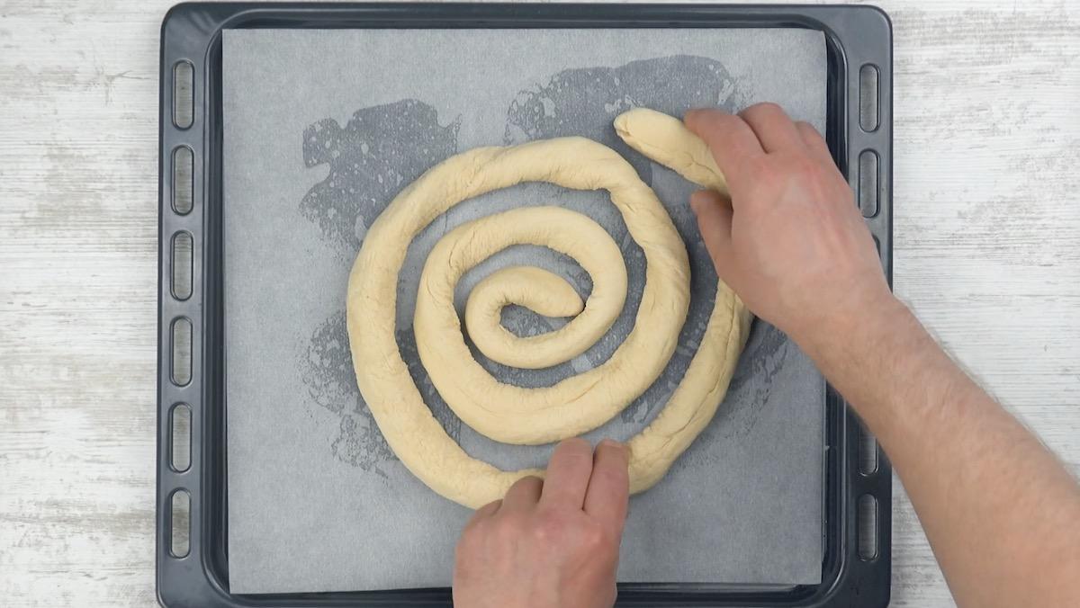 Pasta per pizza ripiena a spirale su una teglia foderata di carta da forno