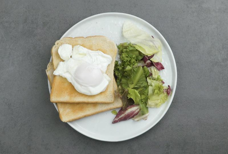 Uova in camicia sopra pane tostato con insalata