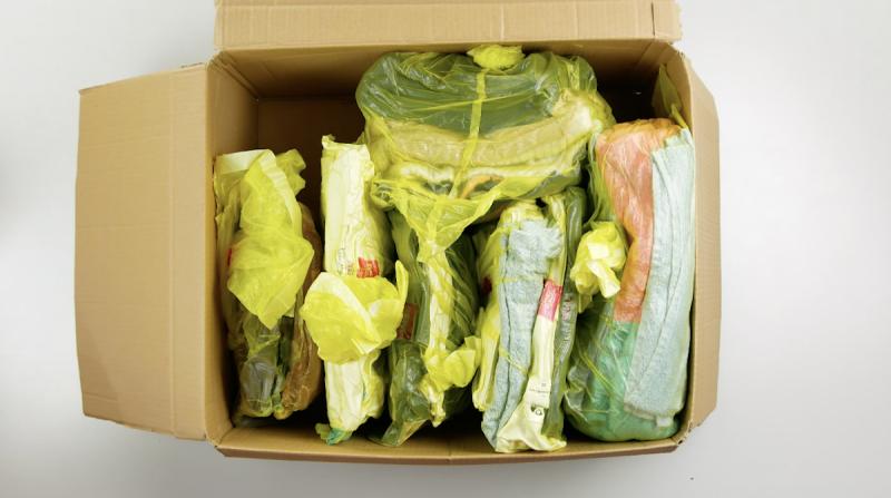 Vestiti imballati in sacchi della spazzatura dentro una scatola di cartone