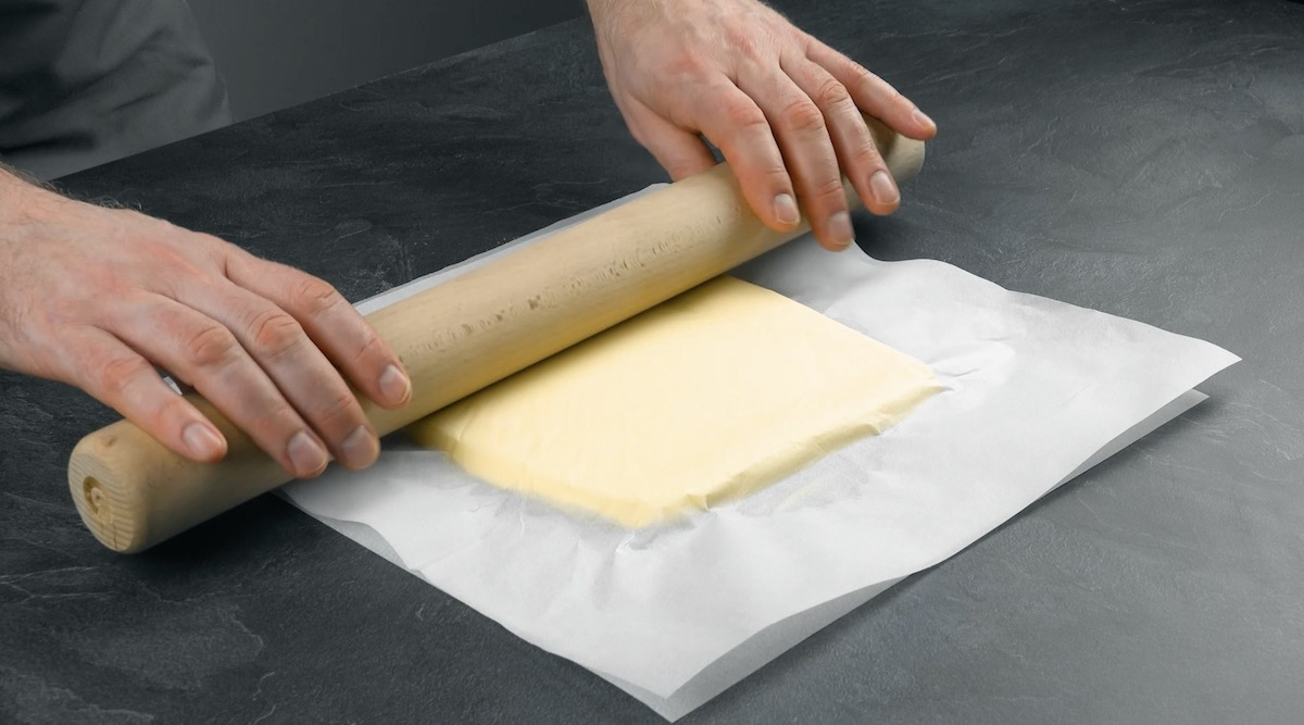 Burro avvolto nella carta da forno steso col matterello