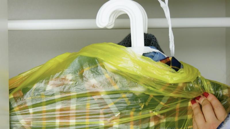 Vestiti con grucce infilati dentro a sacchi della spazzatura