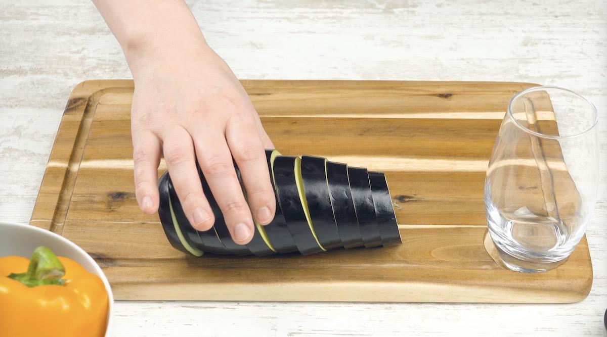 Melanzana tagliata a fette su tagliere di legno