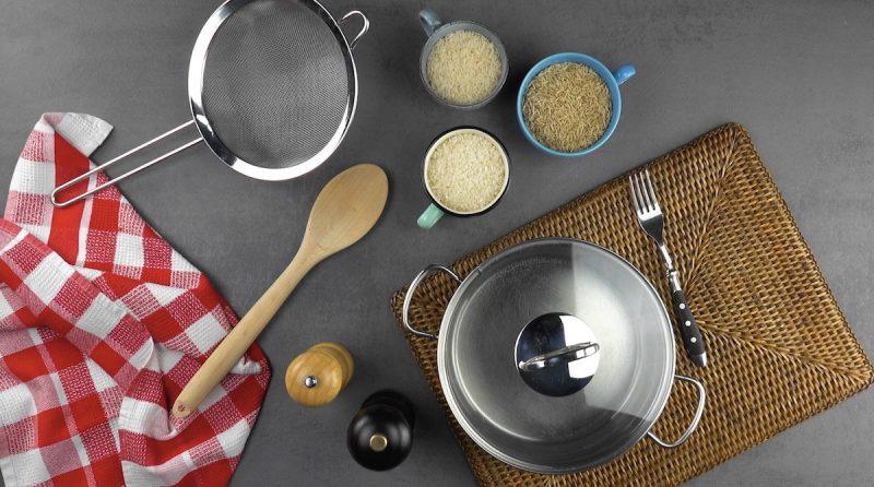 Pentola con coperchio sopra sottopentola, mestolo di legno, forchetta, tre tazze con il riso, colino, canovaccio, saliera e pepiera