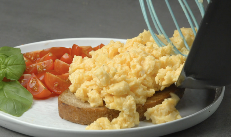 Uova strapazzate su una fetta di pane con pomodorini e basilico