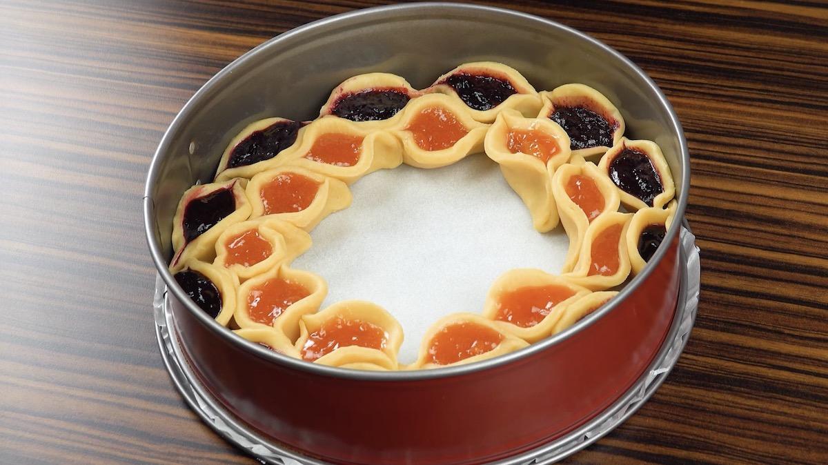 Tasche di pasta frolla ripiene di marmellata alla frutta in verticale in una teglia a cerniera rivestita di carta da forno