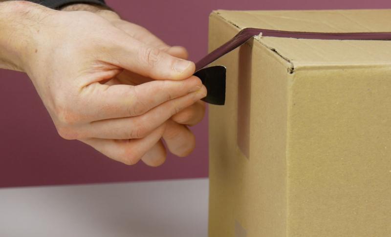 Estremità piegata del nastro adesivo attaccato su una scatola di cartone