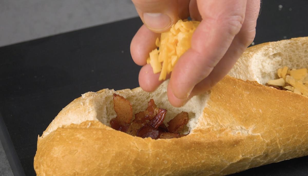 Aggiunta di formaggio cheddar grattugiato insieme alla pancetta tesa