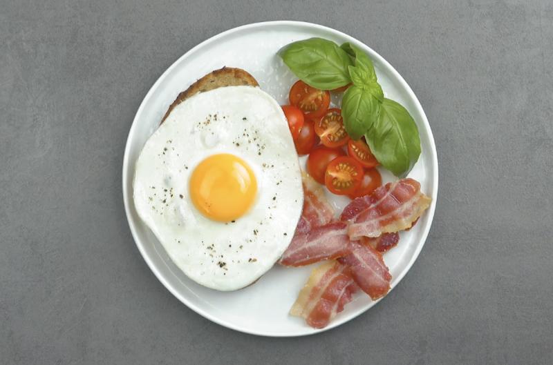 Piatto con uovo al tegamino, pancetta abbrustolita, pomodorini e basilico
