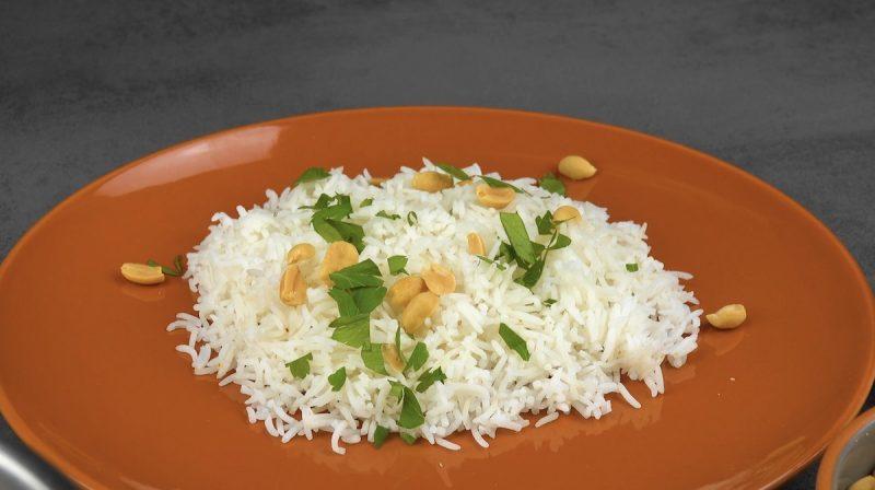Piatto di riso bianco con frutta secca e erbe aromatiche