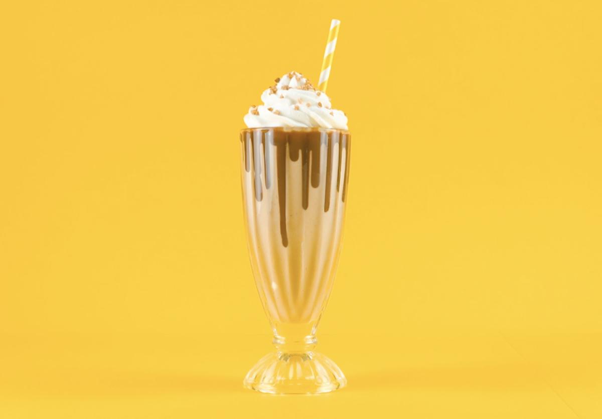 Milkshake alla banana con salsa al cioccolato, panna montata e nocciole tritate