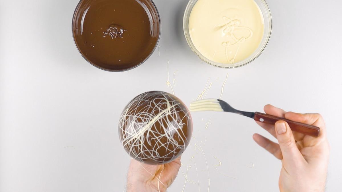 Decorazioni con cioccolato bianco fuso che cola dalla forchetta
