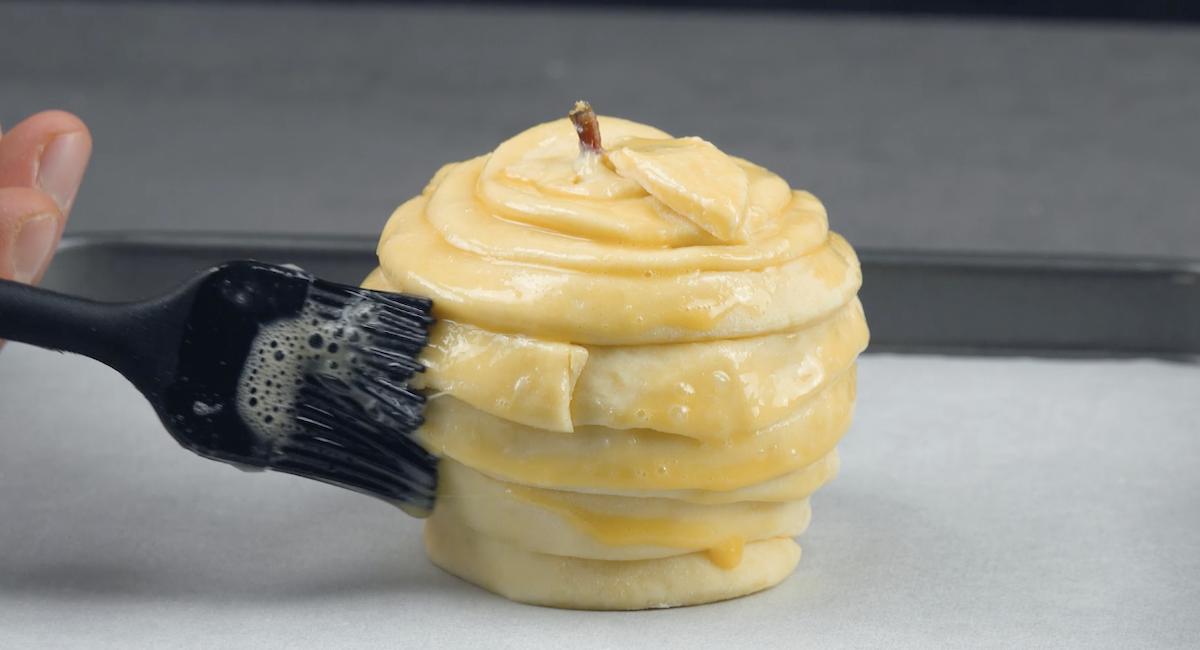 Mela ripiena avvolta nella pasta sfoglia e spennellata con l'uov sbattuto