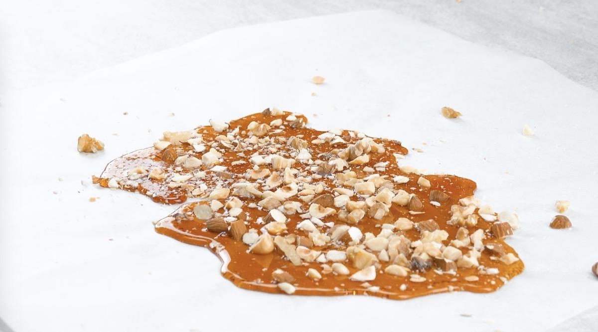 Zucchero caramellato con frutta secca su carta da forno