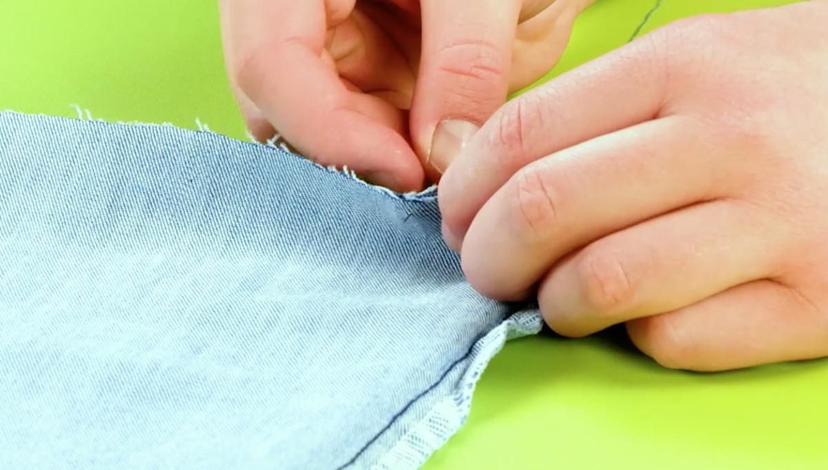 Bordo dei jeans tagliato cucito con ago e filo