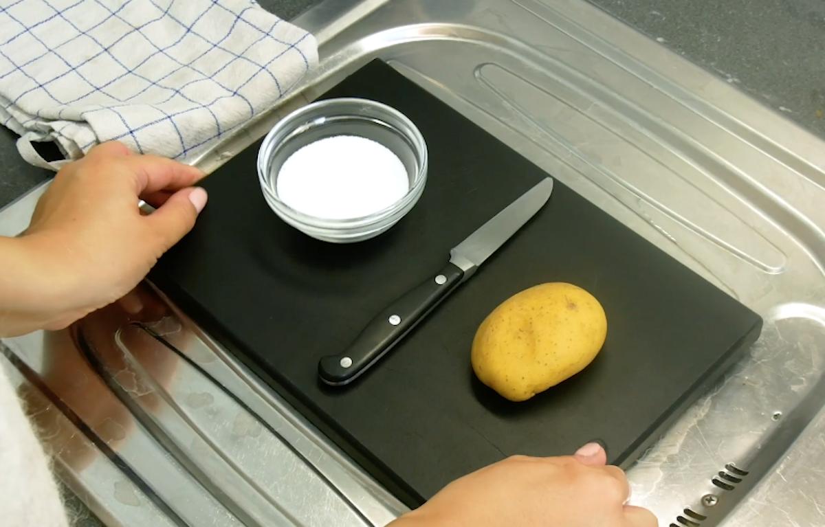 Tagliere con patata, coltello e scodellina di vetro con sale