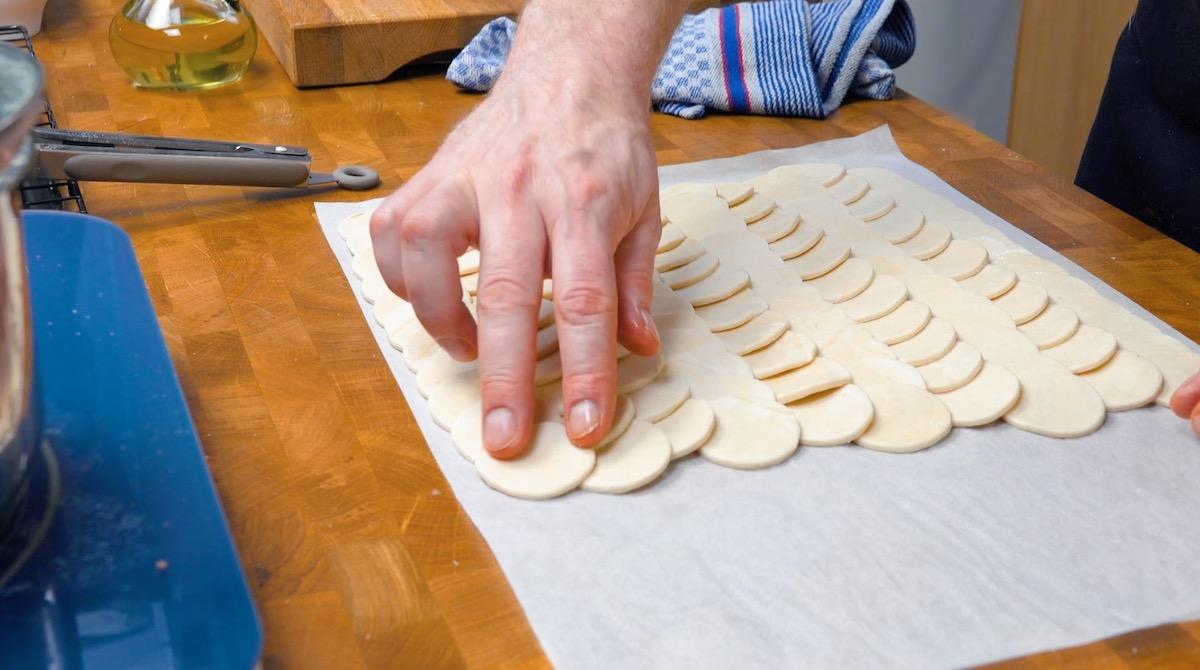 Cesrchi di pasta sfoglia disposti uno accanto all'altro sulla carta da forno