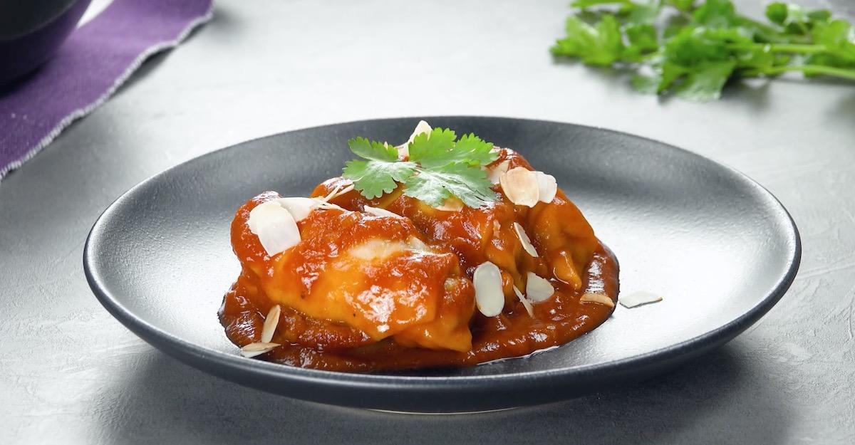 Fagottini ripieni di carne macinata e uva passa serviti con salsa di pomodoro