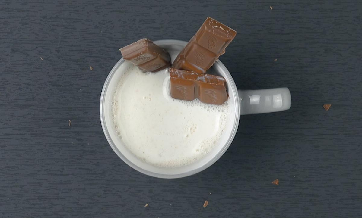 Pezzi di cioccolato fondente in una tazza di latte bollente