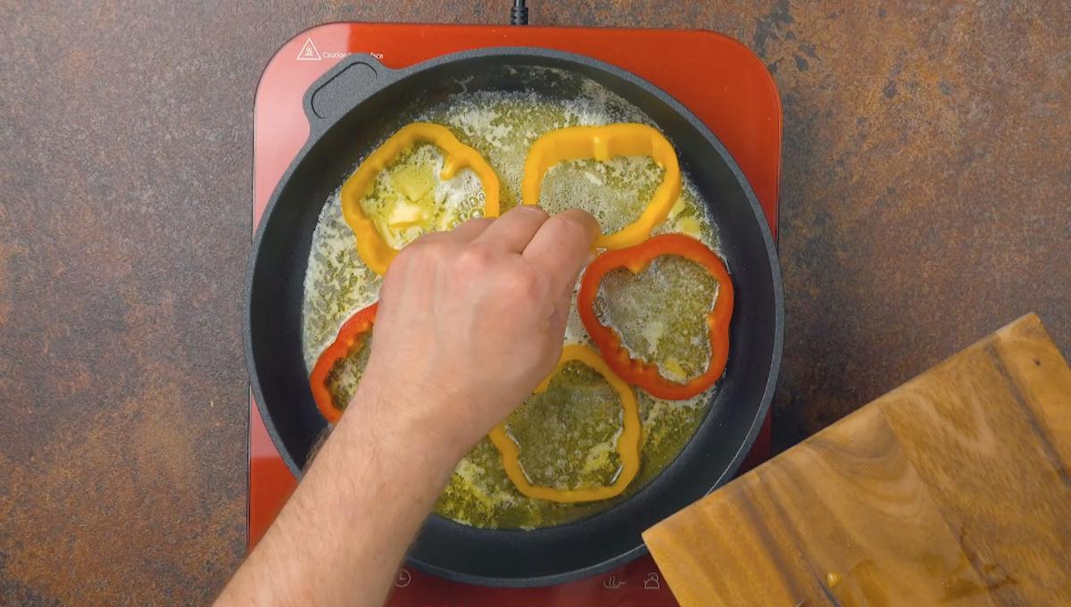 Anelli di peperoni in padella che friggono