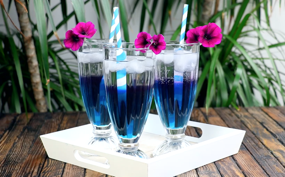 Tre bicchieri di tè freddo blu con cannuccia e fiorellino