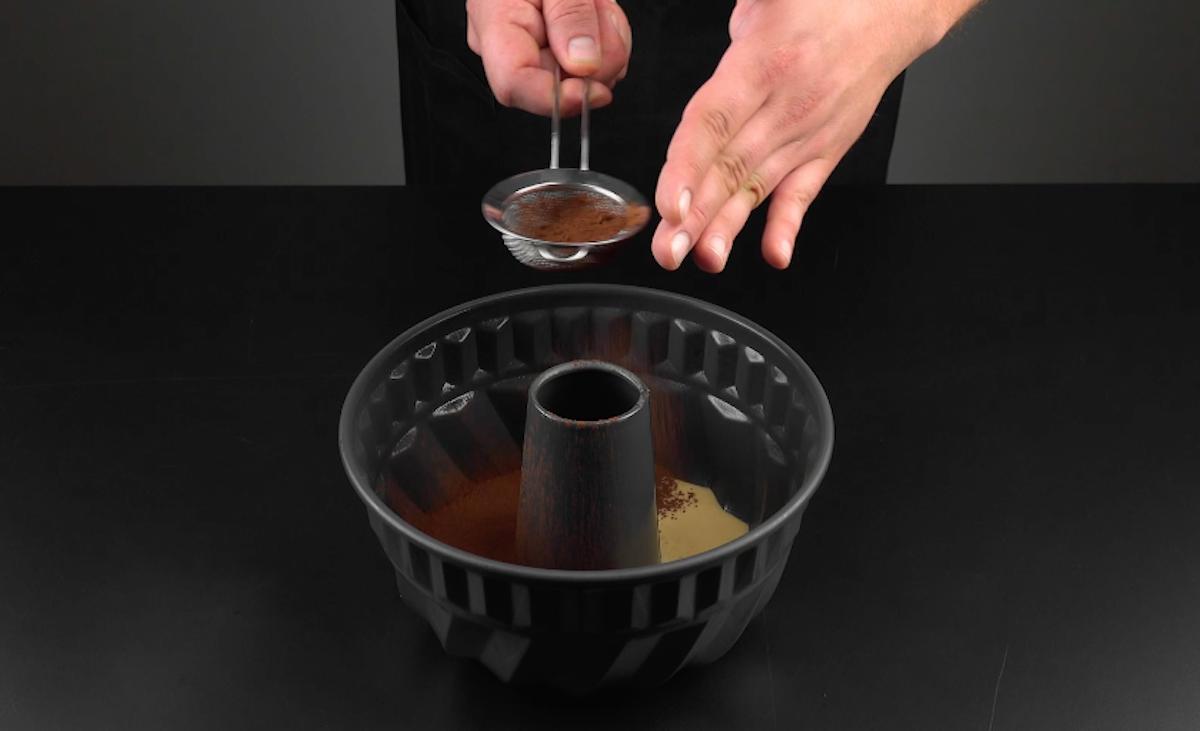 Cacao in polvere setacciato sull'impasto torta nello stampo per ciambellone