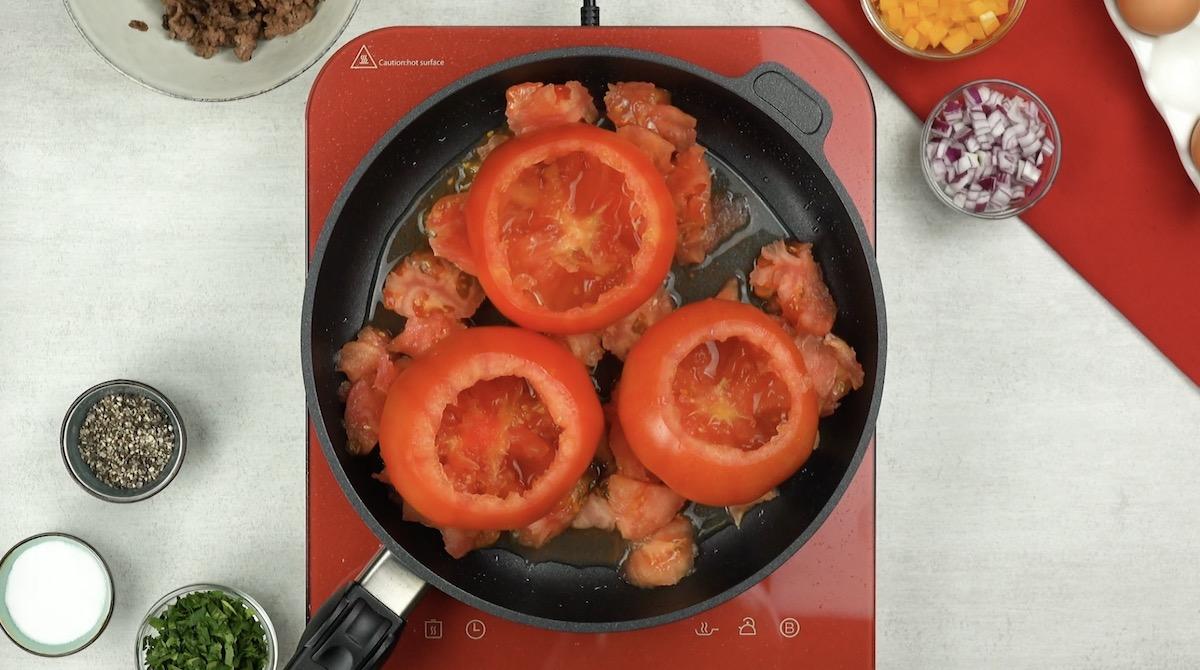 Tre pomodori svuotati con polpa di pomodoro a parte in padella