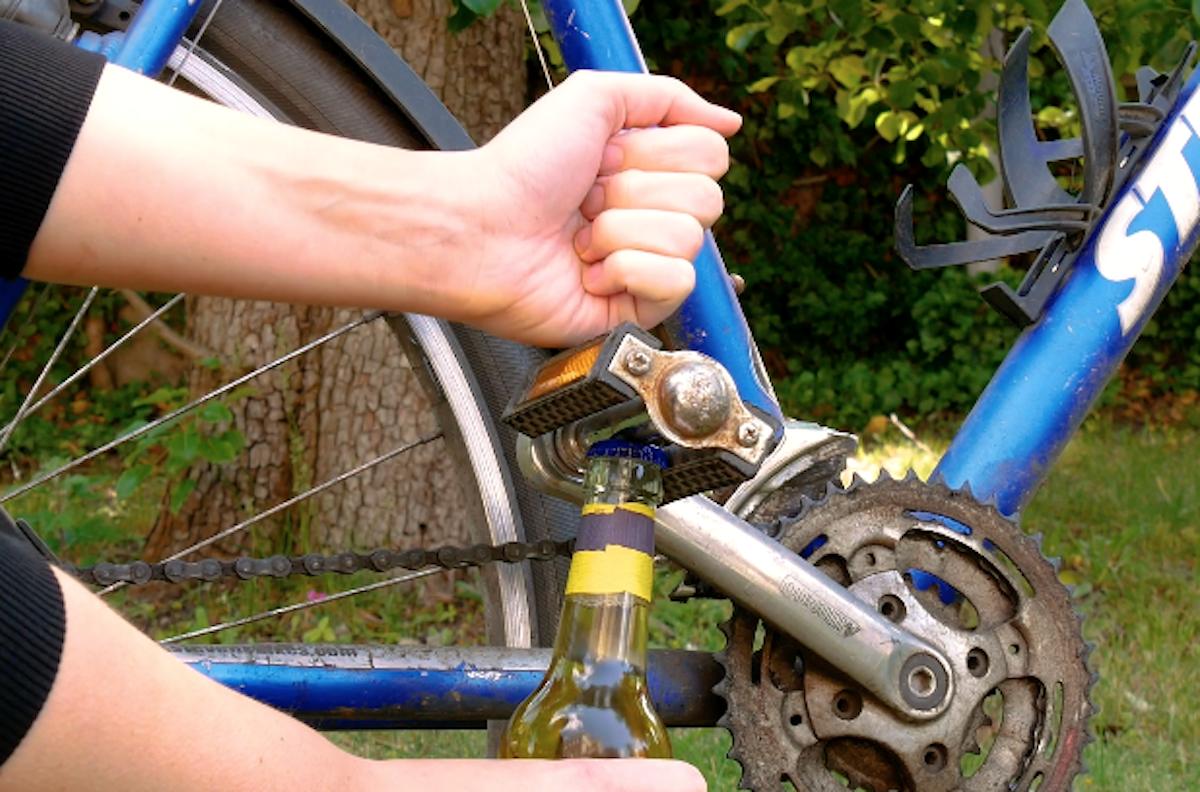 Pedale della bicicletta che apre tappo di bottiglia