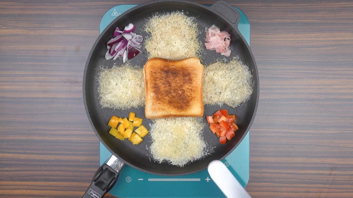 Pane tostato in padella con cipolla, pancetta, peperoni e pomodoro