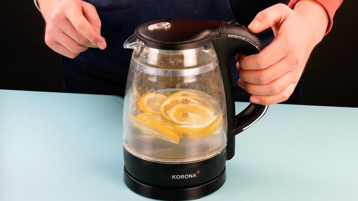 Acqua con fette di limone nel bollitore dell'acqua