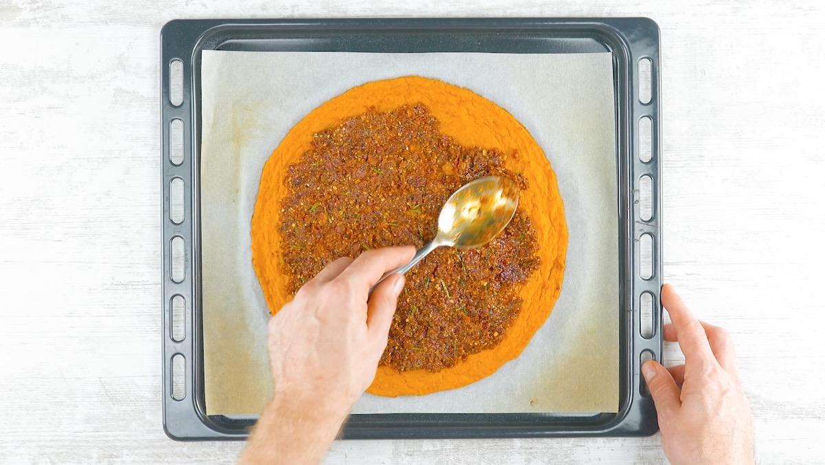 Pesto rosso spalmato sulla pizza di zucca violina