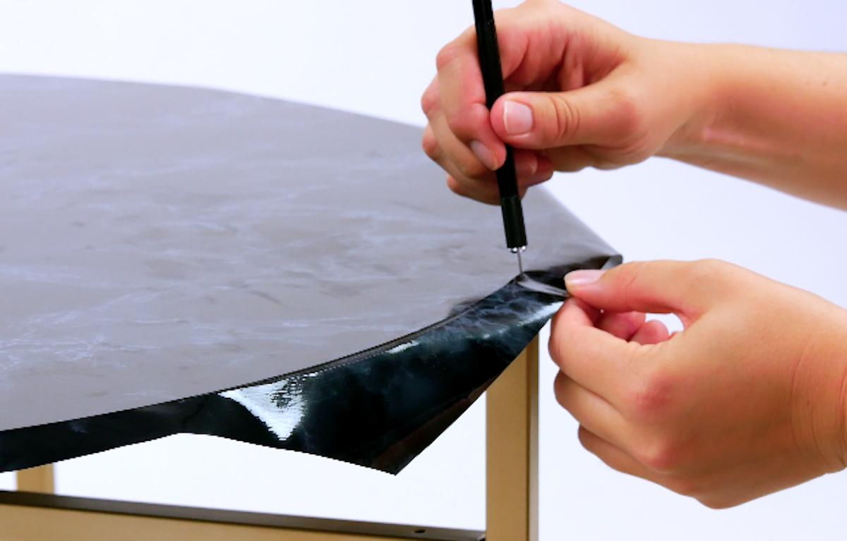Taglio del bordo della pellicola adesiva in eccesso