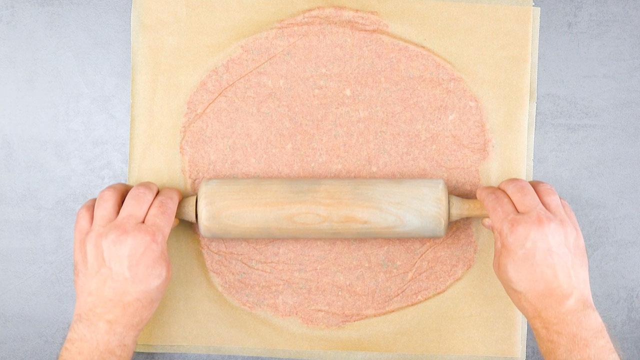 Carne macinata tra la carta da forno stesa col matterello
