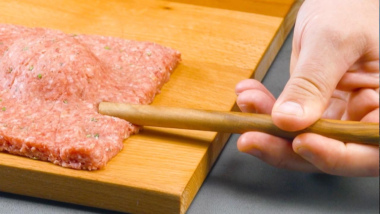 Carne macinata premuta con un cucchiaio di legno