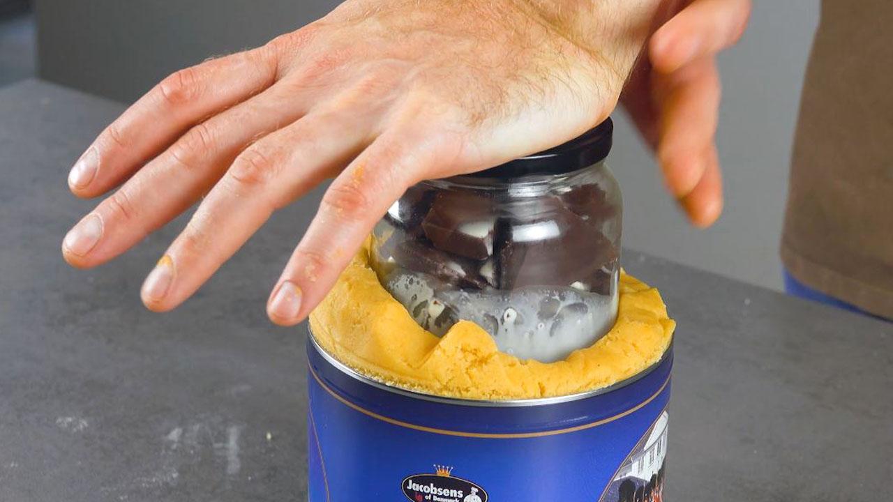 Barattolo di vetro con il cioccolato fondente e la panna liquida nel barattolo di latta con l'impasto